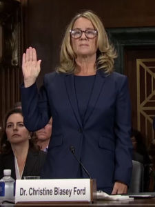 Palo Alto University professor Christine Blasey Ford rises to give an oath prior to her opening statement. Date: 27 September 2018 - wikimedia commons, public domain